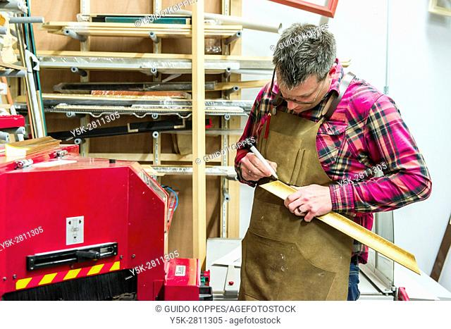 Goirle, Netherlands. Mid adult male craftsman and picture framemaker working on an assignment for a custiomer inside his workshop