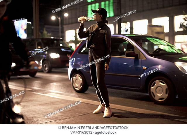 woman drinking from bottle on street in Berlin, Germany