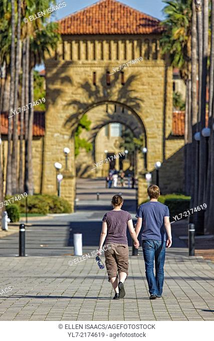 Man and woman students holding hands and walking toward arches leading to Quad on Stanford University campus