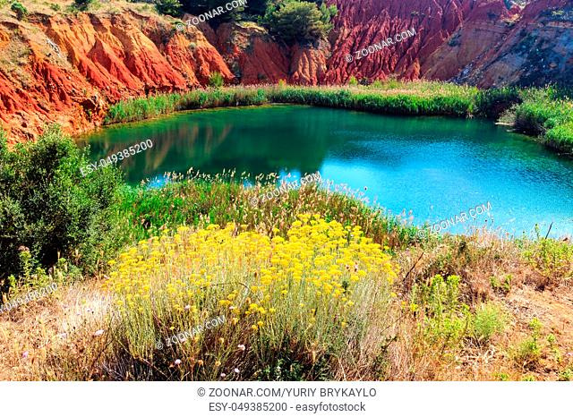 The lake in a old bauxite's red soils quarry cave in Apulia, Otranto, Salento, Italy. The digging was filled with natural waters