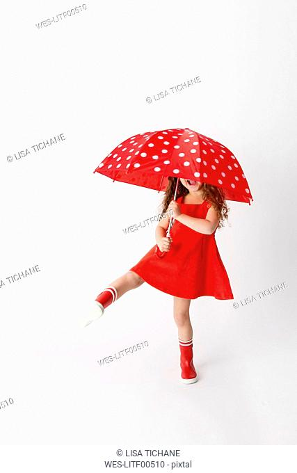 Girl in a red dress and red rain boots holding red umbrella in front of white background