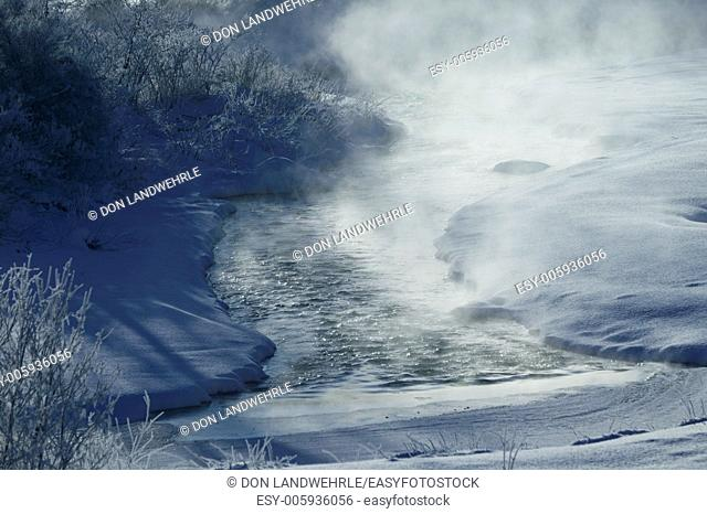 Rising mist from a warm river surrounded by snow covered fields on a cold morning, Stowe, Vermont, USA