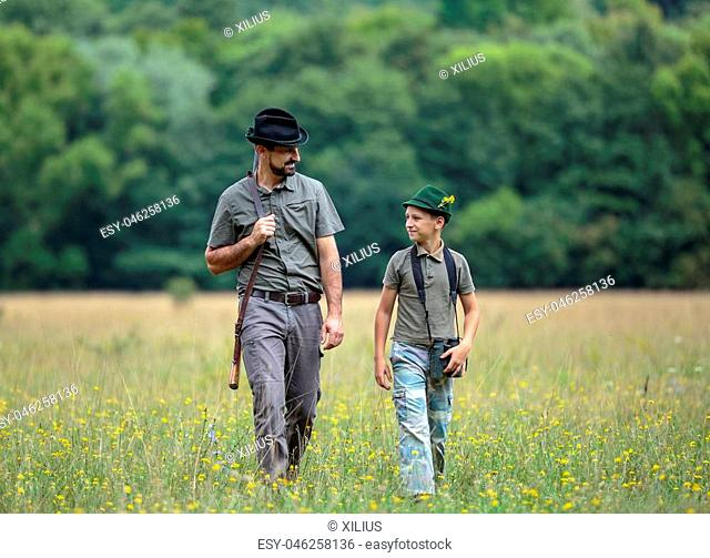 A ranger teaching his son about spotting the game in the wilderness