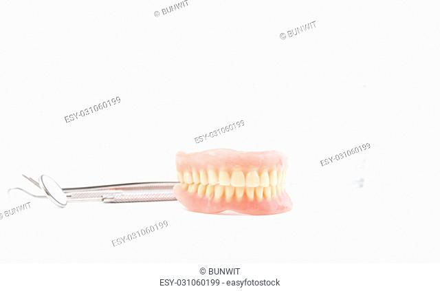 Photo of full dentures with glass of water and dental mirror on white background
