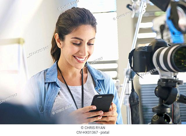 Smiling female photographer using cell phone behind camera in studio