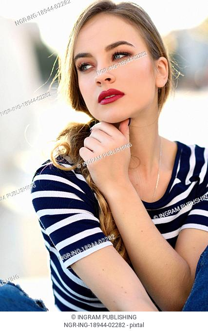 Blonde woman, model of fashion, sitting on a bench in urban background. Beautiful young girl wearing striped t-shirt and blue jeans in the street