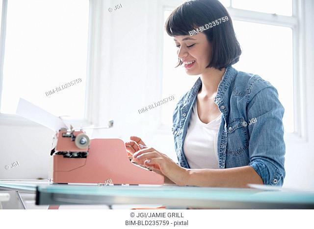 Hispanic woman typing on pink typewriter