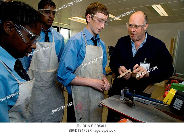 Woodwork teacher showing students how to make a wooden joint in a Design technology lesson