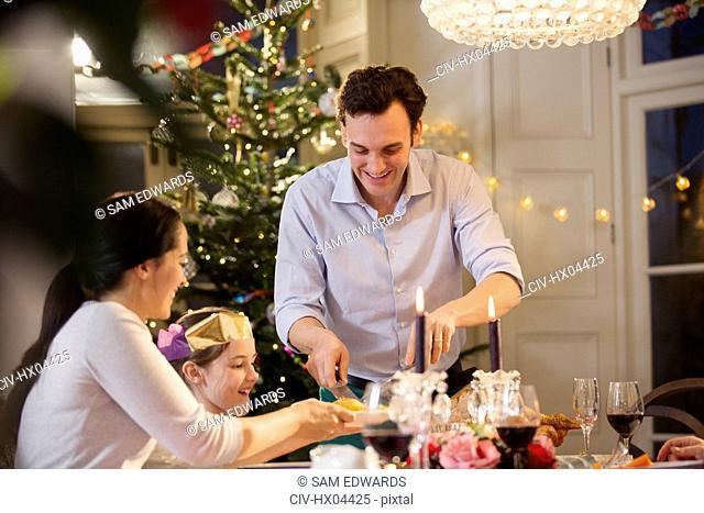 Family enjoying candlelight Christmas dinner