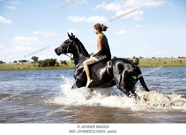 Woman riding horse across river