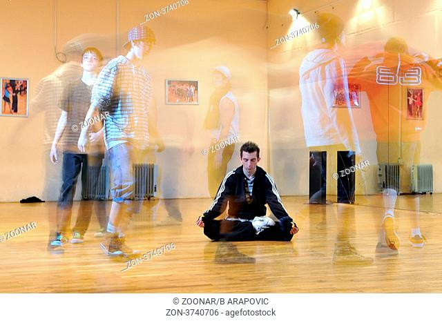 young man meditating in lotus position at dance studio