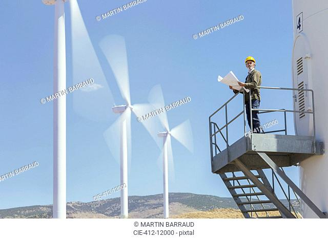 Worker standing on wind turbine in rural landscape