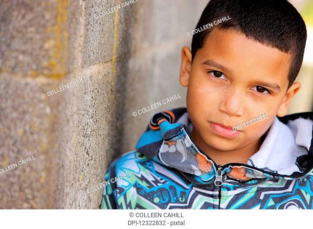 Portrait of a young boy standing against a concrete wall; Oregon, United States of America