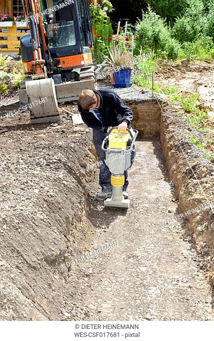 Europe, Germany, Rhineland Palatinate, Man working with soil compactor during house building