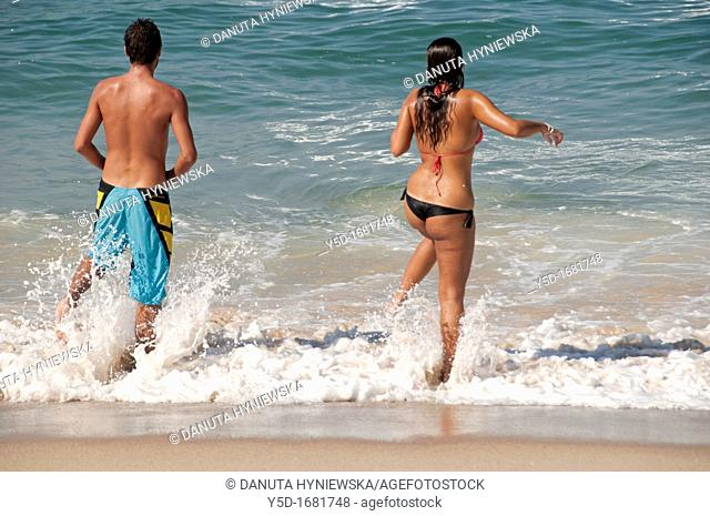 Young couple entering the water on Atlantic Ocean, Portugal, Silver Coast, May