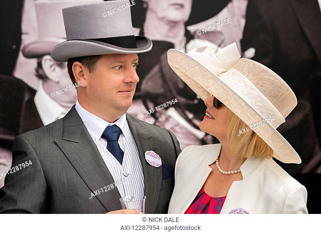A man in grey morning dress with a top hat, blue tie and matching handkerchief and wearing a badge for the Royal Enclosure at Ascot is looking shocked at his...