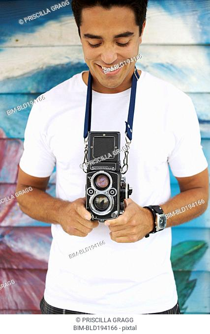 Mixed race man holding old-fashioned camera