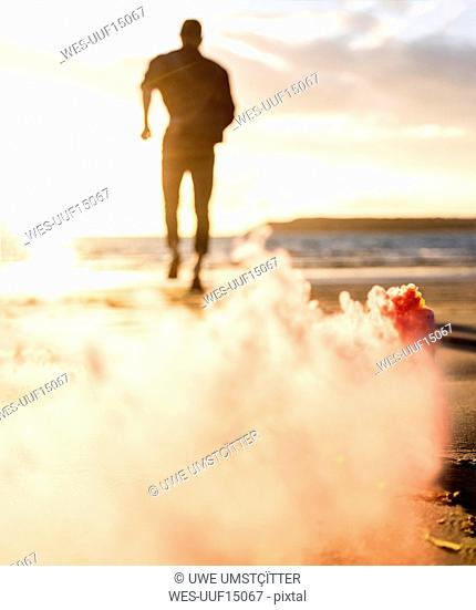 Young man running on the beach at sunset with colorful smoke