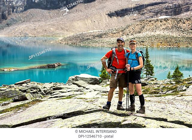 Female and male hiker standing in a large rocky area with colourful alpine lake and mountain cliffs in the background; British Columbia, Canada