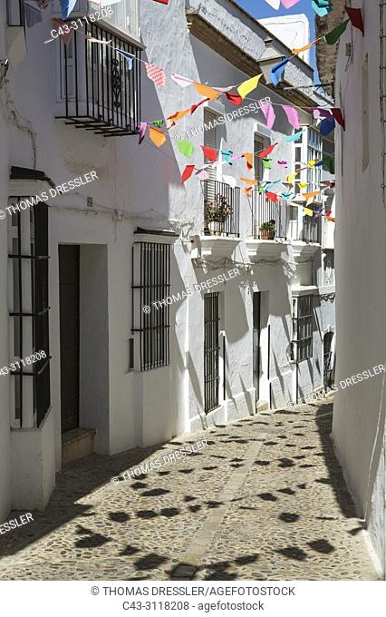 Alley and brilliantly whitewashed, reja (grille) fronted houses in the hilltop White Town of Arcos de la Frontera. The little colourful flags are remains of a...
