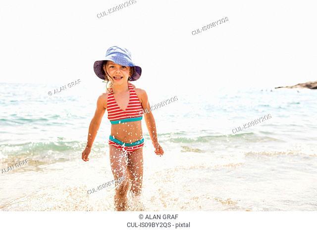 Cute girl in sunhat running in sea, portrait, Portoferraio, Tuscany, Italy