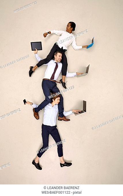Businesswoman carrying colleagues on shoulders while working on mobile devices