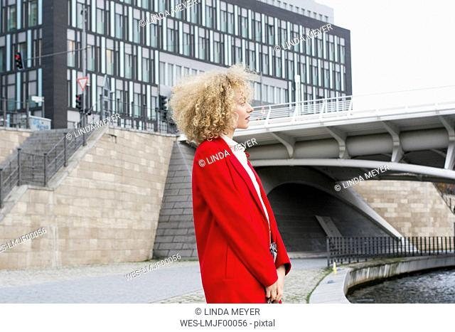 Germany, Berlin, blond young woman with ringlets wearing red coat