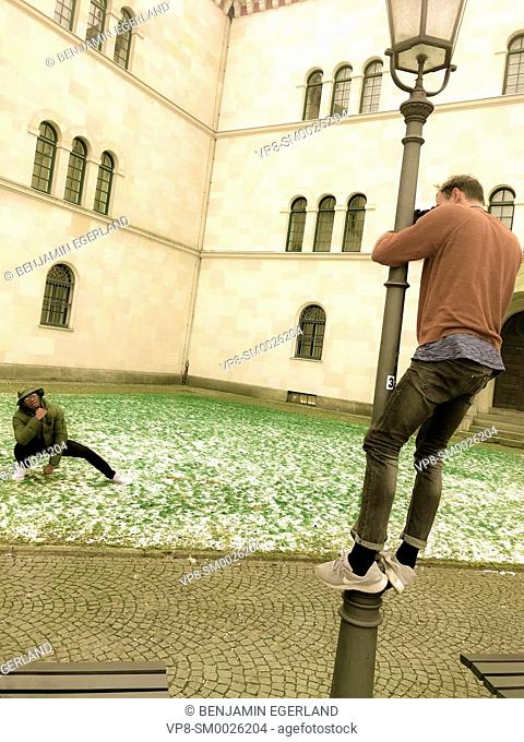 motivated photographer climbing on street lamp to photograph male model from above, at street in city Munich, Germany