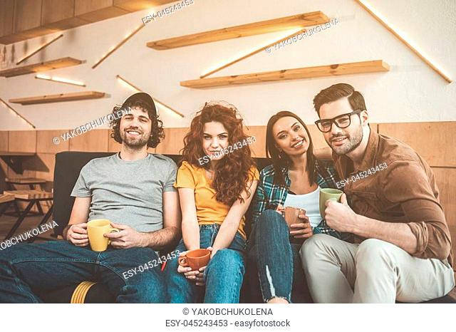 Portrait of relaxed guys and girls sitting on couch in cozy cafeteria. They are holding cups of coffee and smiling