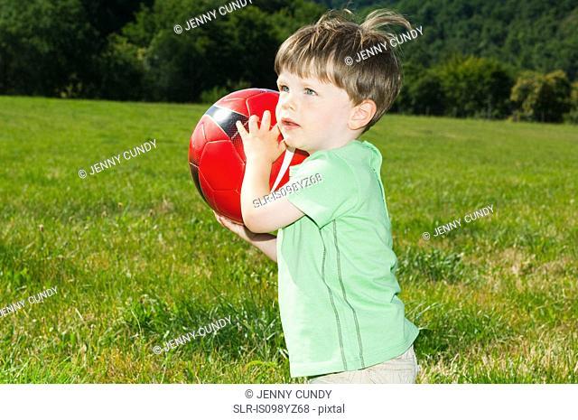 Boy holding football, portrait