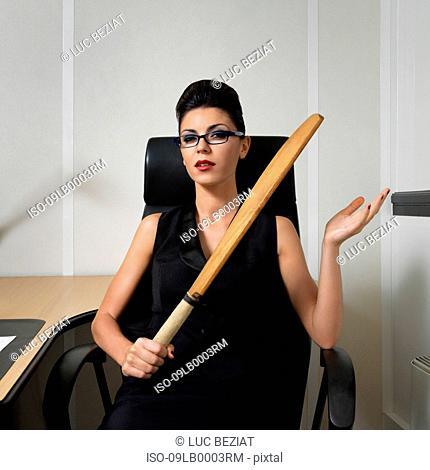 Businesswoman holding a cricket bat