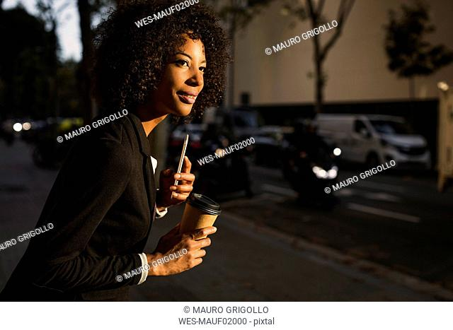Portrait of businesswoman with coffee to go and cell phone waiting at evening twilight