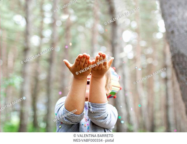 Little boy catching confetti in the woods