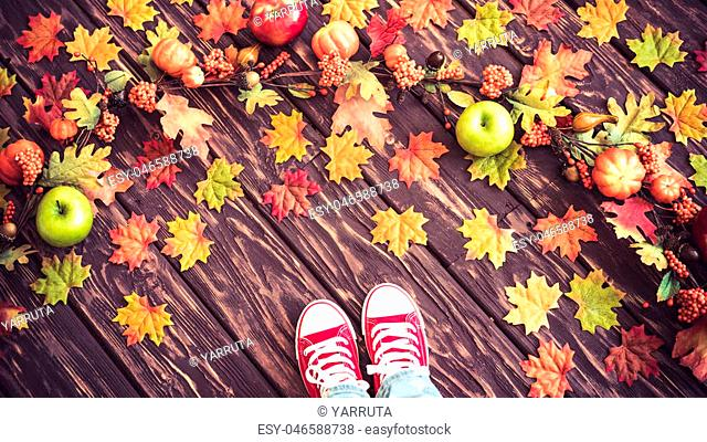 Happy child lying on autumn leaves. Top view portrait of funny kid at home. Thanksgiving holiday concept