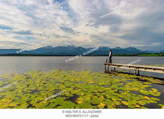 Germany, Bavaria, Allgaeu, Lake Hopfensee, woman standing on jetty