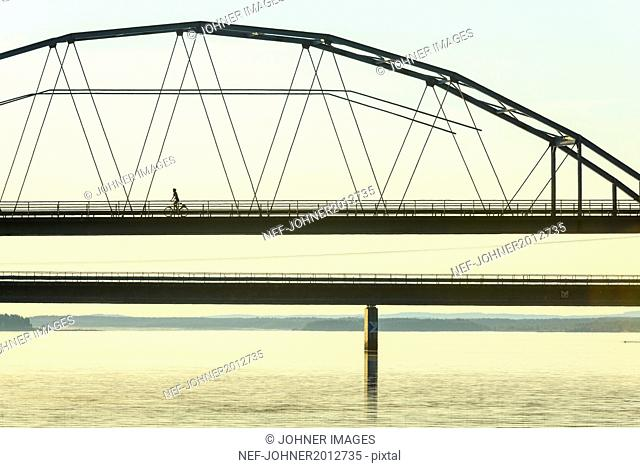 Person cycling through bridge at dusk