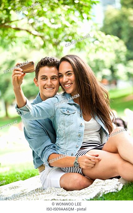 Young couple taking self portrait on camera phone in park, smiling