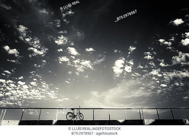 Silhouette of parked bicycle and sky with clouds. Barcelona, Catalonia, Spain