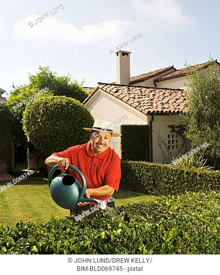 Middle-aged Hispanic man watering hedge