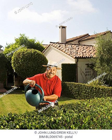 Middle-aged Hispanic man watering hedge