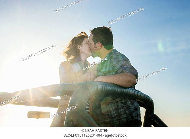 Young couple kissing in pick-up truck