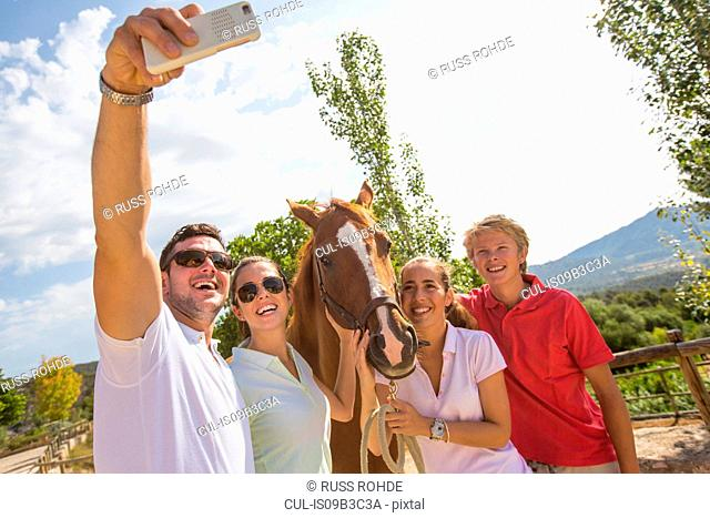 Groom and friends taking smartphone selfie with horse at rural stables