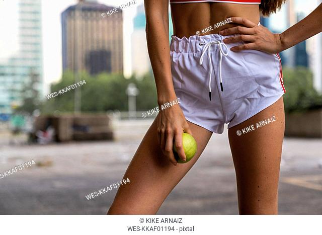 Close-up of young woman wearing gym shorts holding an apple