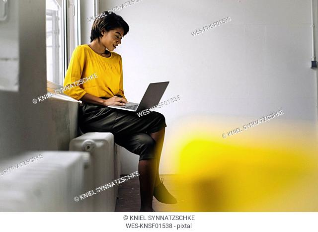 Woman sitting at the window using laptop