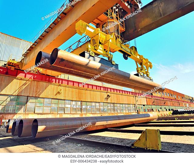 Loading pipes With Bridge Crane on industrial place