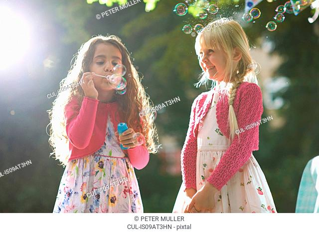 Two cute girls blowing bubbles in sunlit garden
