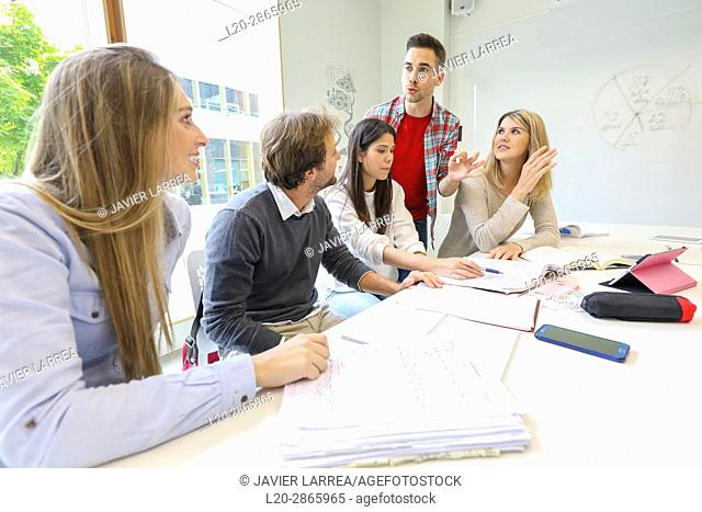 Teacher with group of students doing a joint work, University of the Basque Country, San Sebastian, Donostia, Gipuzkoa, Spain
