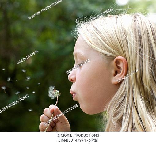 Caucasian girl blowing flower