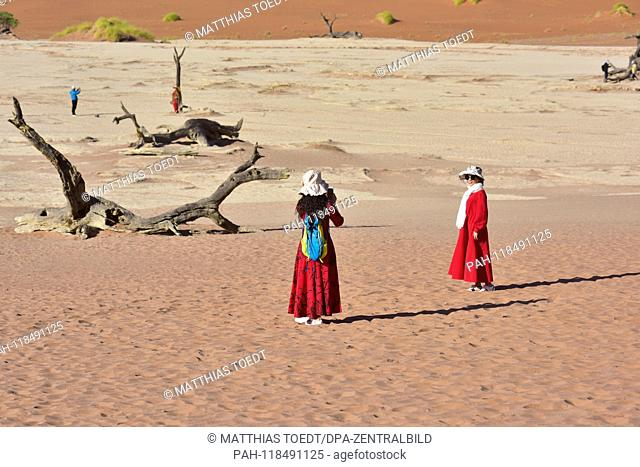 Asian tourists in long, sun-protective clothes take pictures in Dead Vlei, taken on 01.03.2019. The Dead Vlei is a dry, surrounded by tall dune clay pan with...