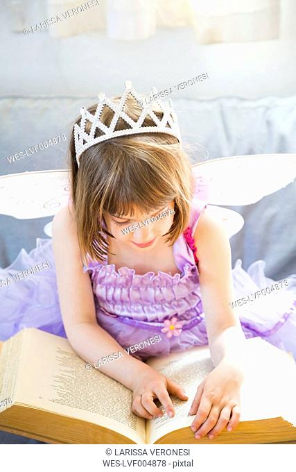 Little girl dressed up as fairy queen reading book